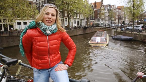 Bild 1 von 2: Die Hauptstadt der Niederlande ist ein Magnet für Touristen aus der ganzen Welt. Vor allem junge Menschen zieht es nach Amsterdam. Moderatorin Andrea Grießmann macht sich auf in die Stadt der 165 Grachten und der 8.863 historischen Gebäude, in die Stadt Rembrandts, der Coffeeshops und des Nachtlebens. Sie schwingt sich aufs Fahrrad und auf diverse Boote und fragt die Amsterdamer: Wie schafft es diese altehrwürdige Stadt eigentlich, so beschwingt, frei und aufgeschlossen zu sein?