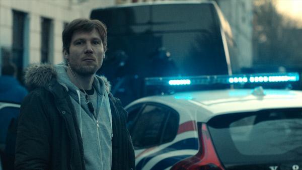 Bild 1 von 5: Polizist Arne (Jeroen Perceval) überwacht die Situation vor der Bank.