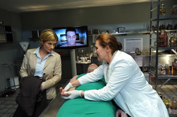 Bild 1 von 15: Die Gerichtsmedizinerin Prof. Lisa Wolter (Eva Maria Bayerwaltes, r.) zeigt SOKO-Kommissarin Martina Seiffert (Astrid M. Fünderich, l.) die Verbrennungen an den Händen des Opfers. Der Schwimmtrainer wurde durch einen Stromschlag getötet.