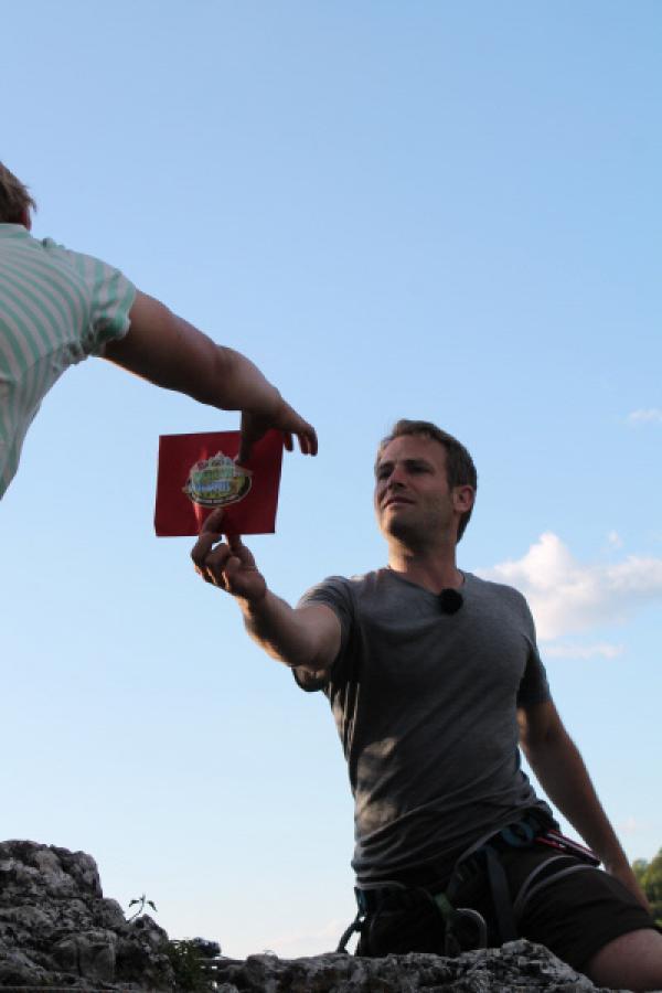 Bild 1 von 1: Wildniscoach Tobi überreicht den ersehnten Umschlag.
