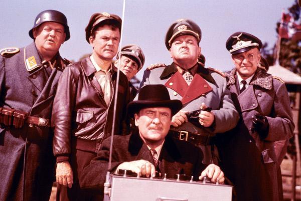 Bild 1 von 3: (Stehend v.l.) Sgt. Hans Georg Schultz (John Banner), Colonel Robert E. Hogan (Bob Crane), General von Kattenhorn (Jacques Aubuchon), Colonel Wilhelm Klink (Werner Klemperer)